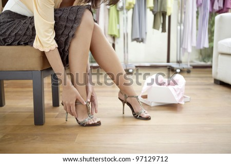 Close up of a young sophisticated woman trying on new shoes in a fashion store.