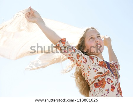 Close up of a young teenage girl holding a sarong in the air, blowing in the wind against a blue sky. - stock photo