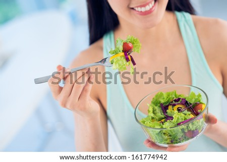 Close-up of a young woman enjoying a freshly cut salad