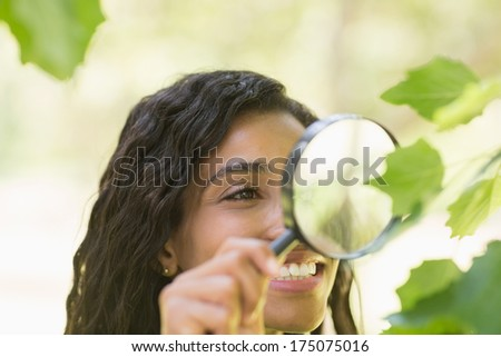 Close-up of a young woman examining leaves with a magnifying glass