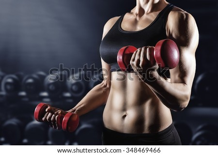 Close-up of a young woman exercising with weights in the gym - stock photo