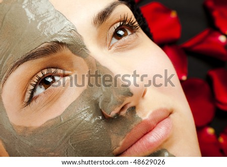 close-up of a young woman face  half with clay mask - stock photo