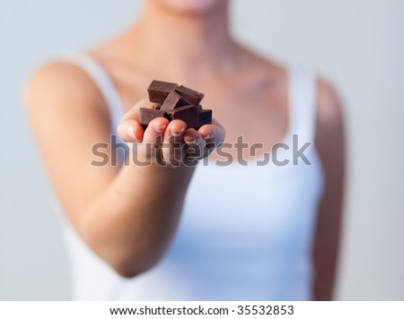 Close-up of a young woman holding chocolate with focus on chocolate - stock photo