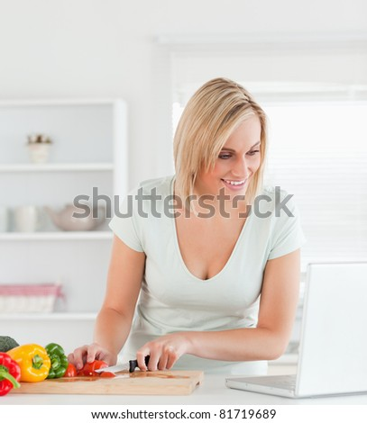 Close up of a young woman looking for a recipe on laptop in the kitchen