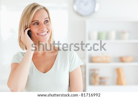 Close up of a young woman on phone in kitchen - stock photo