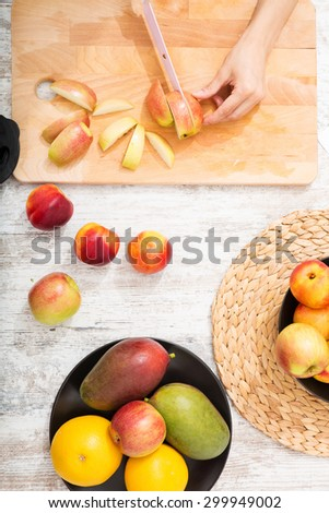 Close-up of a young woman preparing apple juice.