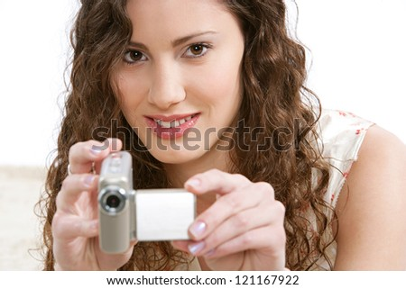 Close up of a young woman recording with a small digital video camera while laying down on a furry carpet in the living room at home, smiling.