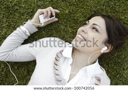Close up of a young woman's face listening to music with earphones, laying down on green grass. - stock photo