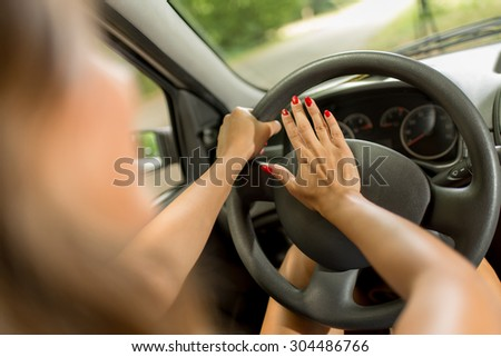 Close-up of a young woman's hand pressing in a car horn - stock photo