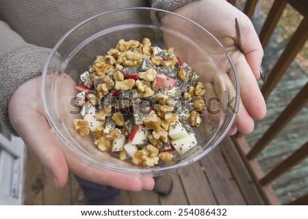 Close up of a young woman's hands holding a glass bowl full of raw and organic apple pieces, walnuts, and black chia seeds - stock photo