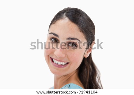 Close up of a young woman smiling at the camera against a white background