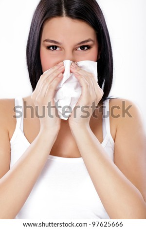 Close up of a young woman sneezing into a tissue - stock photo