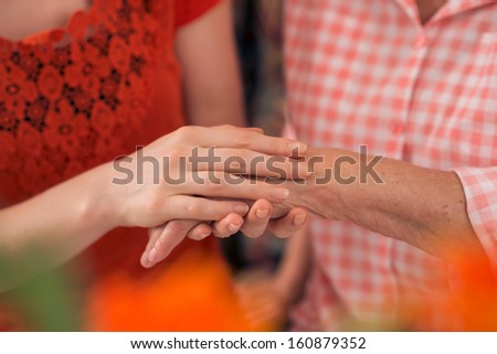 Close-up of a young woman touching a hand of an elderly one with care - stock photo