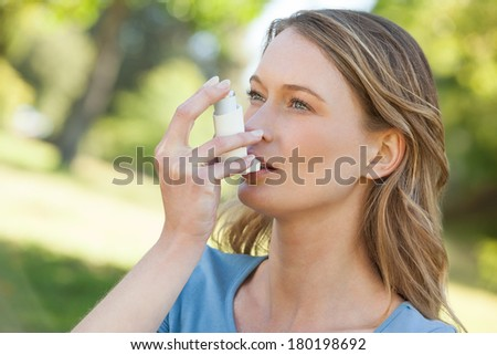 Close-up of a young woman using asthma inhaler in the park - stock photo