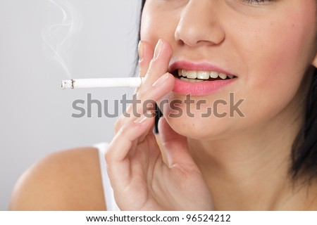 Close up of a young woman with bad skin and yellow teeth, smoking a cigarette - stock photo