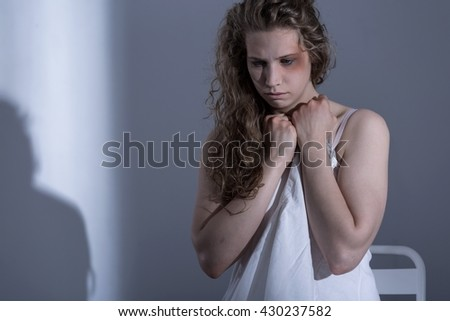 Close-up of a young woman with bruised eye in an empty room, clenching her fists in a manner of despair  - stock photo