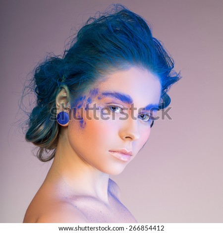 Close-up of a young woman with colorful makeup on a blue background - stock photo