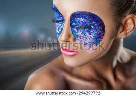 Close-up of a young woman with colorful makeup on background blurred city - stock photo