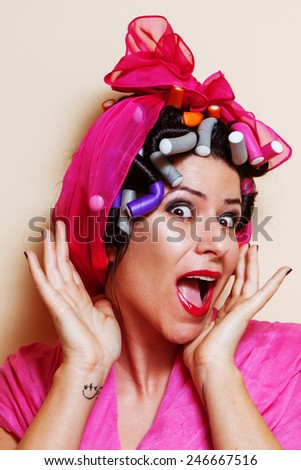 Close-up of a young woman with hair curlers making a surprised grimace
