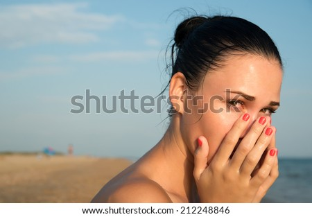 Close-up of a young woman with red eye  rubbing  irritated sensitive eyes or nose on the beach, allergy reaction - stock photo