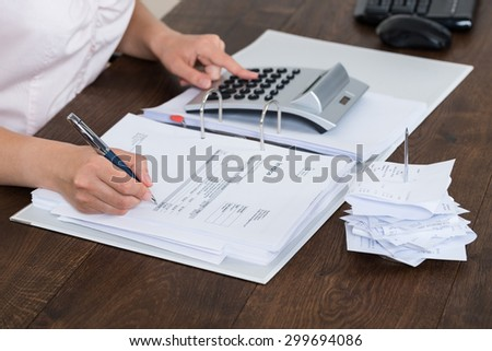 Close-up Of Accountant Calculating Receipt In Office - stock photo
