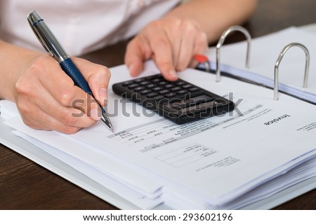 Close-up Of Accountant Doing Calculation With Calculator In Office