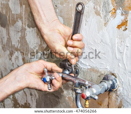 Close-up of adjustable spanner in the hands of plumbing, nut unscrews wall mount kitchen faucet water supply with two handles.