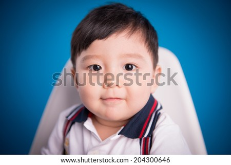 close up of adorable baby boy looking at camera. Isolated on blue - stock photo