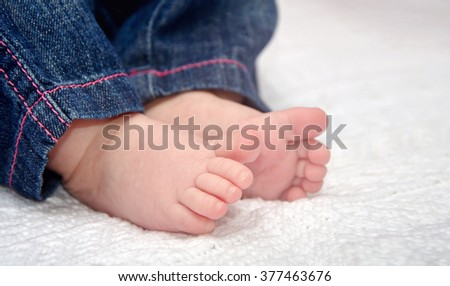 Close up of adorable baby feet on blanket, focus on one foot - stock photo