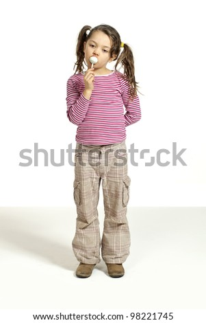 Close-up of adorable little girl with a lollipop
