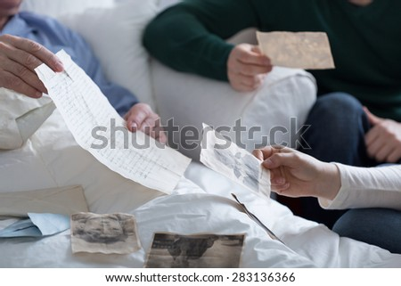 Close-up of adult children browsing father's old photos - stock photo