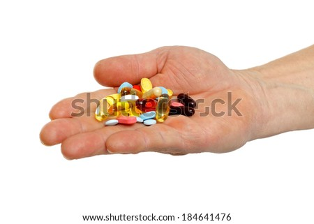 Close up of adult hands holding colorful pills - stock photo