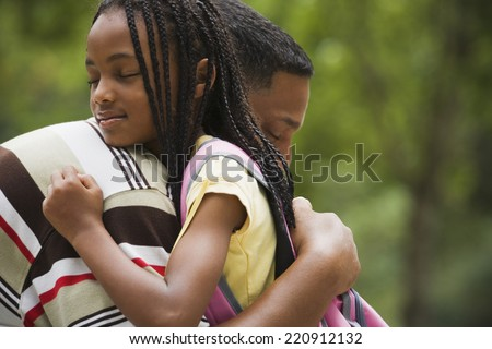 Close up of African father and daughter hugging - stock photo