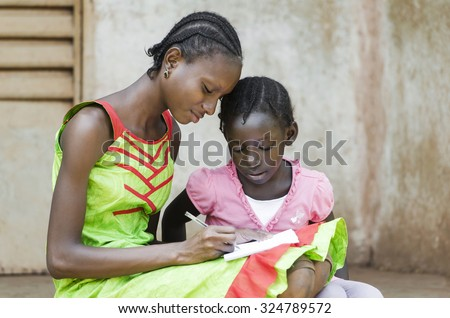 Close-Up of African Girls Learning. Education Symbol: Couple of African Children Studying at School. Beautiful Outdoor shot of two black girls repeating their lessons. - stock photo