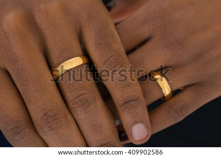 close up of african hands wearing golden rings - African Wedding Rings