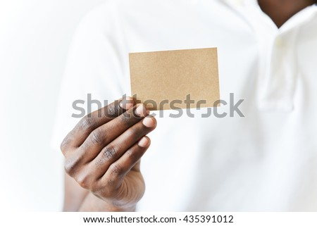 Close up of African man's hands holding business card with copy space for your text or advertising content. Black male wearing white polo shirt showing blank parchment card at the camera. Film effect - stock photo
