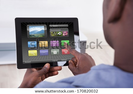 Close-up Of African Person Holding Digital Tablet Showing Icons - stock photo