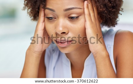 close up of african young woman touching her head - stock photo