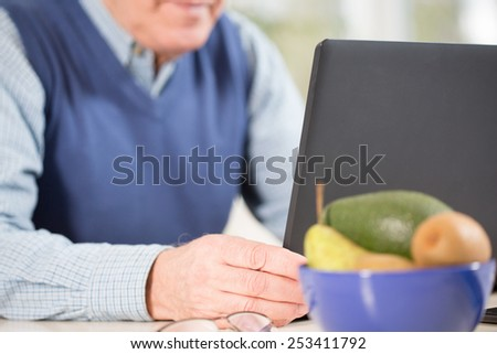 Close-up of aged businessman using laptop - stock photo