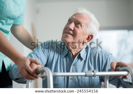 Close-up of aged man trying to stand up with walker - stock photo