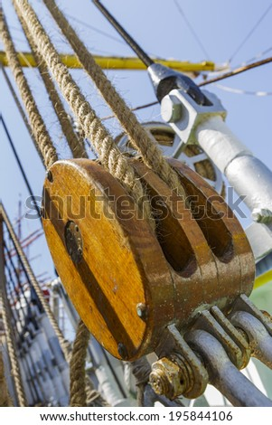 Close-up of aged vintage marine ropes and wooden double tackle block on old sailing vessel. - stock photo
