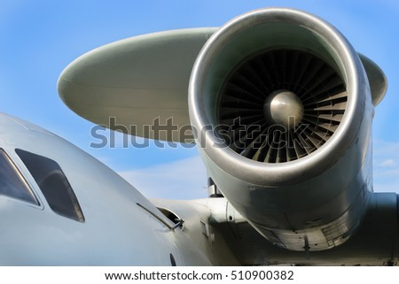 Close up of airplane jet engine, parts of the aircraft fuselage and the tail on cloudy sky background