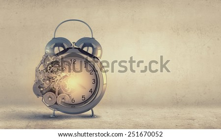 Close up of alarm clock and cogwheel mechanism - stock photo