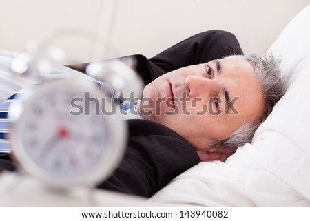 Close-up Of Alarm Clock In Front Of Man Sleeping - stock photo