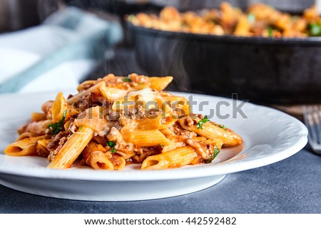 Close up of american chop suey - pasta dish with beef, tomato sauce, mozarella cheese, spices and parsley. Italian-American cuisine. White plate with steaming hot pasta and pan with rest dish on back - stock photo