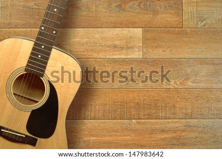 Close up of an acoustic guitar on a wooden floor, shot from above