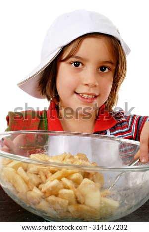 Close-up of an adorable elementary girl smiling over the apple slices she's stirring in with apple pie spices.  On a white background. - stock photo
