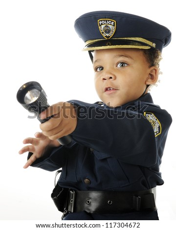 Close-up of an adorable preschool policeman in uniform shining his flashlight.  On a white background.