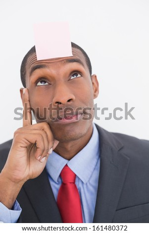 Close up of an Afro businessman with blank note on forehead over white background - stock photo