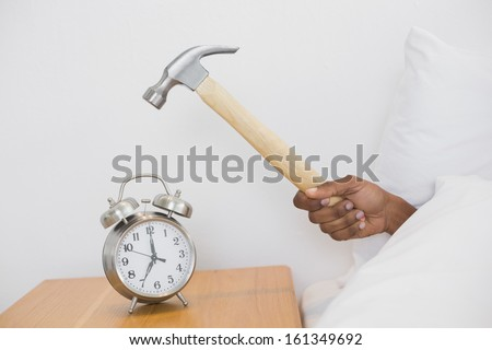 Close up of an Afro man's hand smashing alarm clock with hammer in bed at home - stock photo